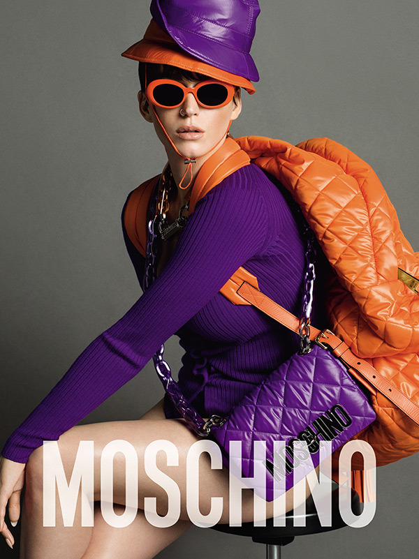 Perry in bold purple and orange hats combined with purple sweater and Moschino handbag to create a colorful campaign