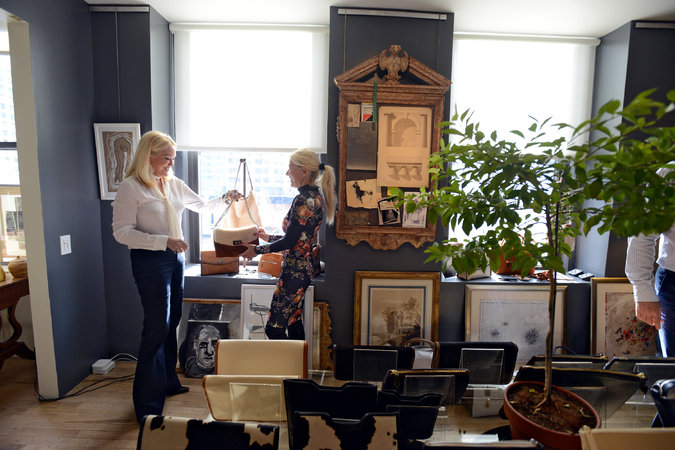 Nina Griscom standing on the left attending to her customer at her 2015 Fall Handbag Trunk show. Courtesy: nytimes.com